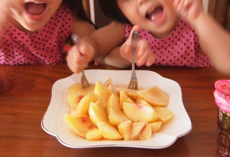 桃を食べるこどもたち